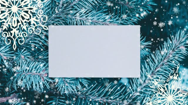 Video Christmas background with fir branches, snowflakes and golden balls. Top view with letter and copy space