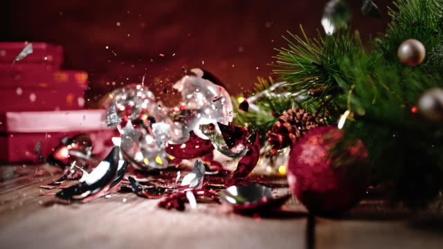 slo mo christmas balls falling on the floor, crushed into pieces - jodła filmów i materiałów b-roll