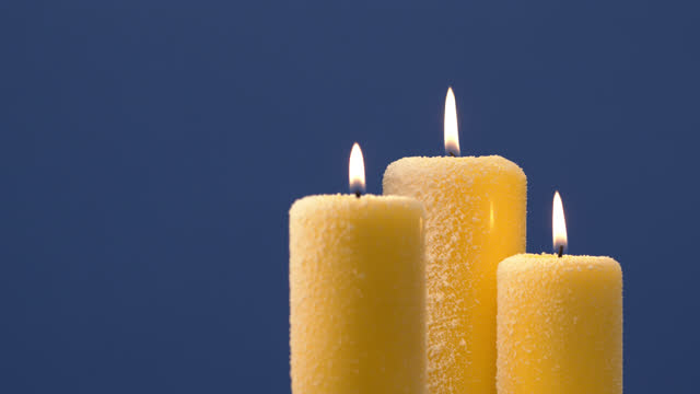 Christmas candles with tongues of flame on a blue background in the snow close up.