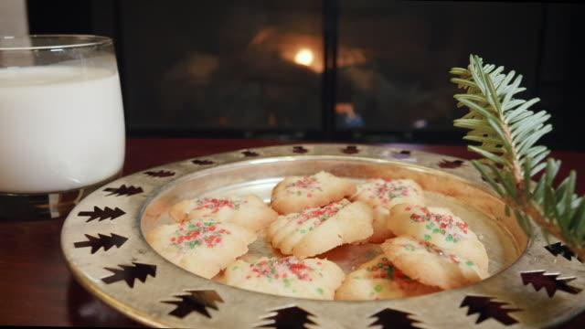 vidéos et rushes de biscuits de noël et du lait pour le père noël devant une cheminée en 4 k - saint nicolas