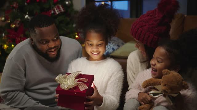 stockvideo's en b-roll-footage met kerstdag, happy black family thuis. afrikaanse amerikaanse vader, moeder en kind het openen schijnen lichte kerstgiftdoos. leuke dochter die opgewekt en gelukkig met heden voelt. - afro amerikaanse etniciteit