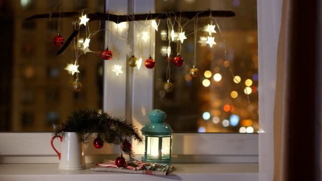Christmas decoration and lantern with candle on a window sill video