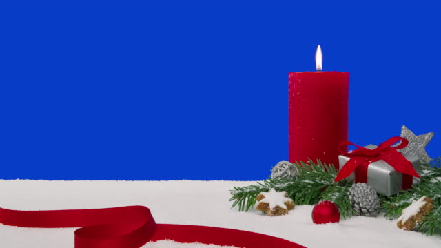 Christmas decoration arrangement on a snowy table in front of a blue screen A Christmas decoration arrangement with a red candle, fir branches, a wrapped gift, scattered decoration elements and a red ribbon on a snowy table in front of a blue screen. The candle is lit and burning with a beautiful flame. weihnachten stock videos & royalty-free footage
