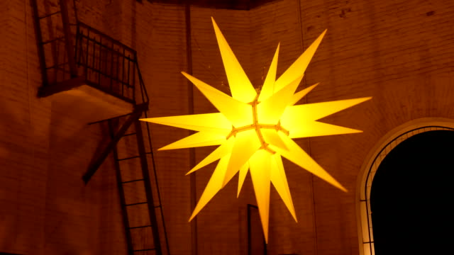 Christmas decoration: huge bright gold star in the darkness. video