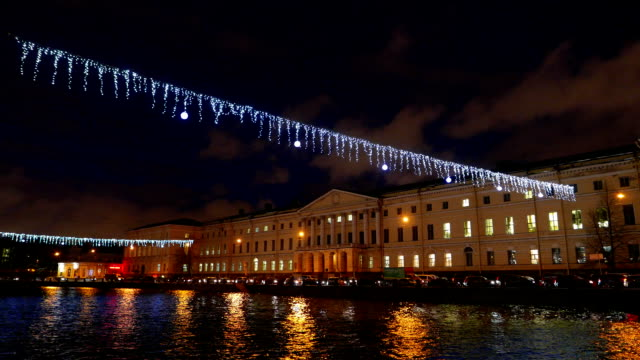 Christmas decoration over Neva river, night city, car traffic on river bank video