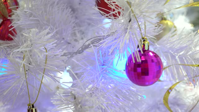 Christmas decorations in the Department store. The Christmas tree is white. Focus on the pink ball.