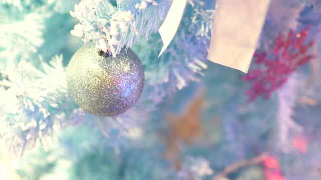 Christmas decorations in the Department store. The Christmas tree is light blue. Focus on the silver ball.