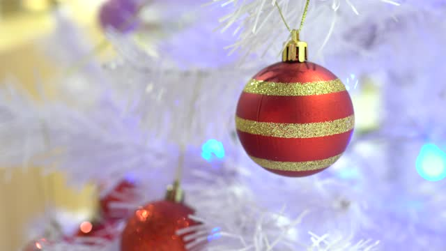 Christmas decorations in the Department store. The Christmas tree is white. Focus on the golden ball. The subject is on the right.