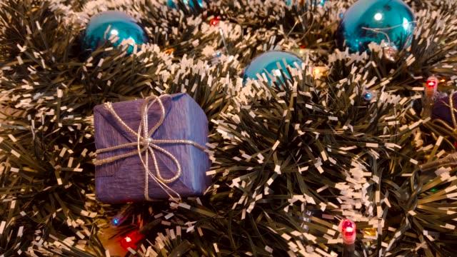 weihnachtsdekorationen mit blauen weihnachtskugeln, verschneiten pinienzapfen, goldener spitze und einem verschneiten weihnachtsbaum, der girlande sieht. - kieferngewächse stock-videos und b-roll-filmmaterial