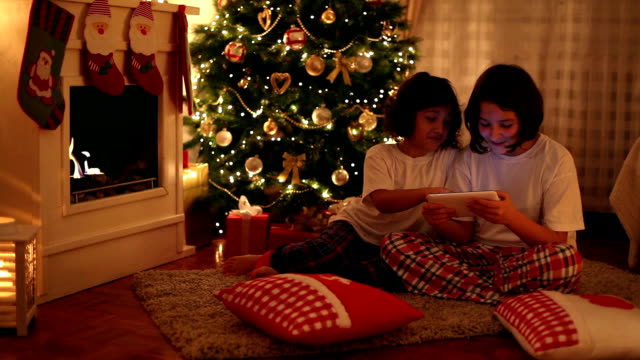 Christmas Evening Two beautiful little girls enjoying on the Christmas Eve while spending time together. They use a digital tablet in front of a fireplace near a Christmas tree christmas stocking stock videos & royalty-free footage