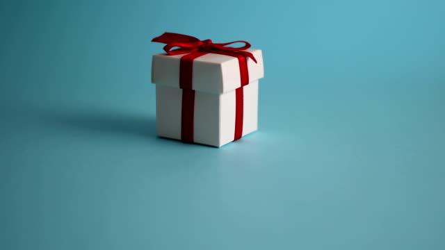 vídeos de stock, filmes e b-roll de presente de natal, garimpando com fundo azul - agradecimento