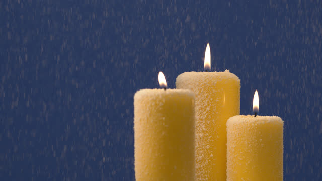 Christmas holiday candles with tongues of flame in a snowy blizzard close up.