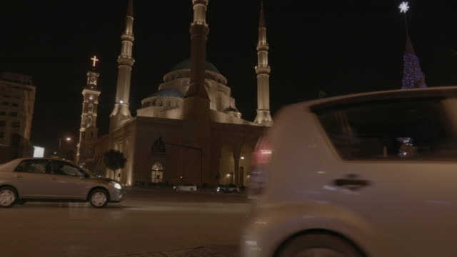 Christmas in Beirut BEIRUT, LEBANON - CIRCA 2016: CU time lapse night view of a policeman directing traffic in Martyr Square in Beirut at Christmas time near the Mohammad al-Amin mosque and St. George Maronite cathedral. beirut stock videos & royalty-free footage