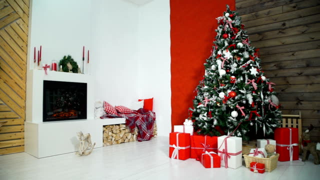 Christmas Interior with Firepace and Christmas Tree Beautiful Christmas Interior with Fireplace and Decorated Christmas Tree in Red and White Colors christmas tree stock videos & royalty-free footage