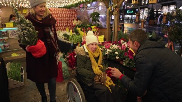 Christmas is the Time for Giving A front-view shot of a family buying gifts for their physically impaired daughter from a small business Christmas market stall in the city, they are wearing warm clothing on a cold December night. small business saturday stock videos & royalty-free footage