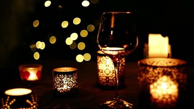 Christmas lights and candles flicker while someone pours wine into the glass video