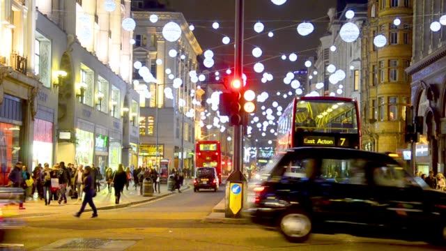 christmas lights and london buses at the station on busy oxford street london, england, united kingdom. oxford circus at traffic rush. - londra video stock e b–roll