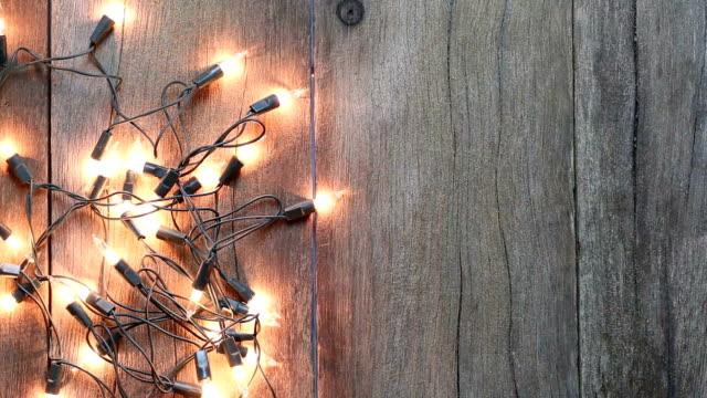 vídeos de stock e filmes b-roll de christmas lights on wooden floors. - christmas table