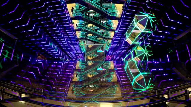 stockvideo's en b-roll-footage met kerst mall winkelcentrum roltrappen en liften en kopers met het winkelen van kerstmis. liften en roltrappen verplaatsen samen met bezoekers in winkelcentrum atrium. reflectie in glazen balustrades liften en roltrappen - christmas tree