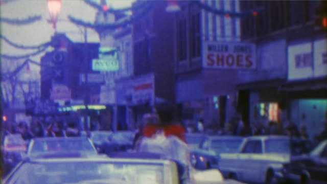 1967: Christmas parade small downtown city old timey storefronts.