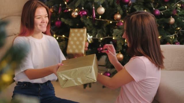 stockvideo's en b-roll-footage met kerstfeest vrolijke zusters uitwisselen van geschenken - uitwisselen