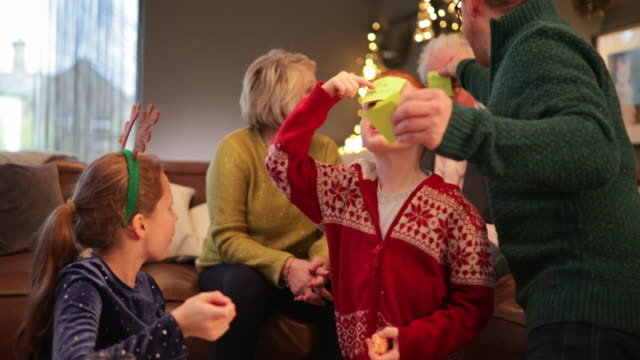 Christmas Party Games Father sticking sticky notes onto his families heads including his children and parents while they play a game at Christmas. They re also eating mince pies. christmas fun stock videos & royalty-free footage