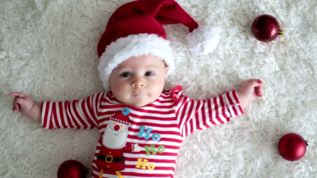 christmas portrait of cute little newborn baby boy, dressed in christmas clothes and wearing santa hat, studio shot, winter time - christmas background стоковые видео и кадры b-roll