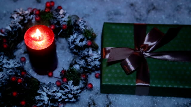 christmas present with a brown ribbon on the background of artificial snow and a lighted candle - nastro per capelli video stock e b–roll