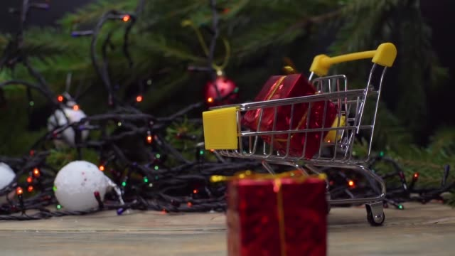 Christmas sale. Gifts fall in mini-basket, trolley, on background of LED garlands