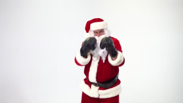 Christmas. Santa Claus on a white background wears black boxing gloves and fulfills punches. Kickboxing, fighter