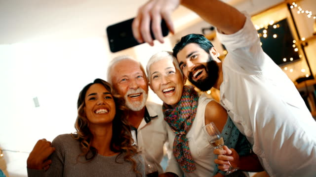 Christmas selfie. Closeup of a senior couple taking selfies with their grandson and his girlfriend at a Christmas party at home. There are three selfies taken, 4k, handheld. party social event stock videos & royalty-free footage