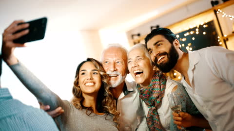 Christmas selfie. Closeup of a senior couple taking selfies with their granddaughter and her boyfriend at a Christmas party at home. There are three selfies taken, 4k, handheld. holiday event stock videos & royalty-free footage
