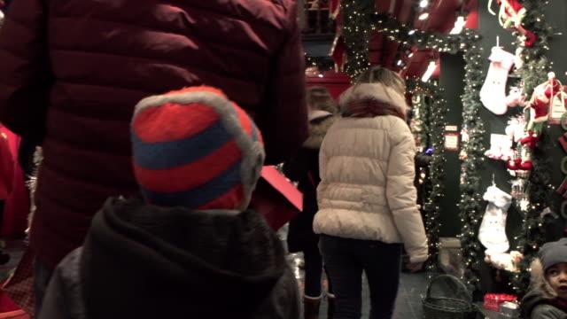 stockvideo's en b-roll-footage met kerstinkopen mix race familie winkel uitvoering presenteert - christmas tree