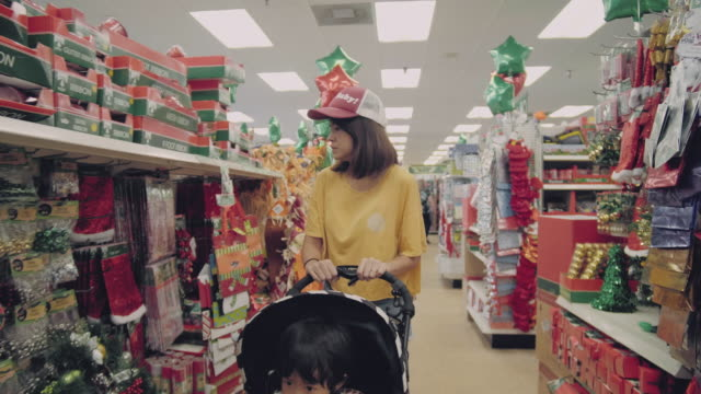 Christmas Shopping Store Carrying Presents Asian family shopping during sales in shopping mall. christmas stocking stock videos & royalty-free footage