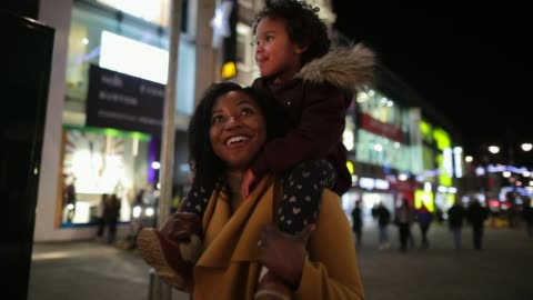 Christmas Shopping with Mummy A close-up shot of a cute little girl sitting on her mother's shoulders, they are having a fun night together shopping for Christmas gifts. carefree stock videos & royalty-free footage