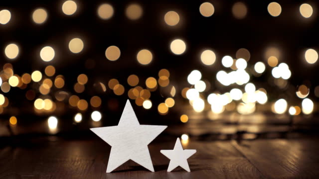 christmas stars on old wooden table light bokeh - tavolo legno video stock e b–roll