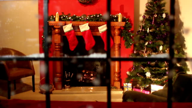 Christmas stocking fireplace scene looking through window - Snow falling Stock HD video clip footage of a Christmas scene shot through a window looking into a Lounge with an open fire and christmas tree. The Stockings are hung up on the fireplace all ready for Christmas Eve. There is also a garland hanging on the mantelpiece.  christmas stocking stock videos & royalty-free footage