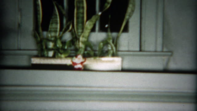 1955: Christmas stockings hanging above the fireplace revealed after a tour. video