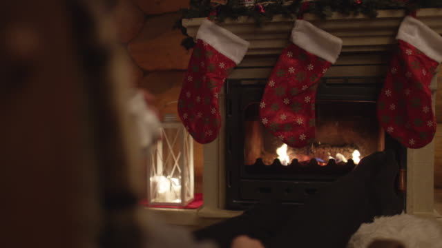 christmas stockings hanging on a fireplace - уютный стоковые видео и кадры b-roll
