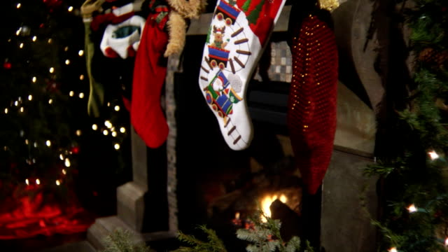 Christmas stockings with fireplace Dolly shot of Christmas stockings and blazing fire underneath christmas stocking stock videos & royalty-free footage