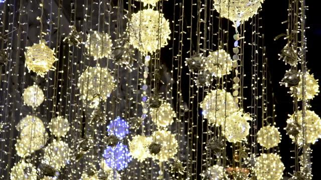 weihnachten straßenbeleuchtung in moskau auf nikolskaya straße. stadt ist für den urlaub mit leuchtenden kugeln an seilen aufgehängt und im wind vor dem hintergrund flackernden bokeh swies dekoriert - bling bling stock-videos und b-roll-filmmaterial