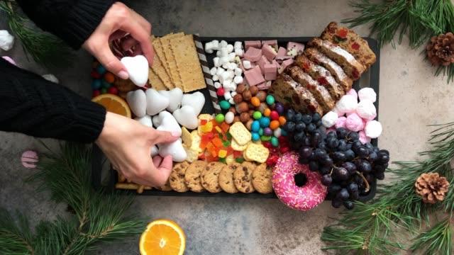 piatto dolci natalizi. torta di frutta di natale, caramelle, cioccolato, canna da zucchero, biscotti, frutta su vassoio nero, vista dall'alto. - christmas table video stock e b–roll