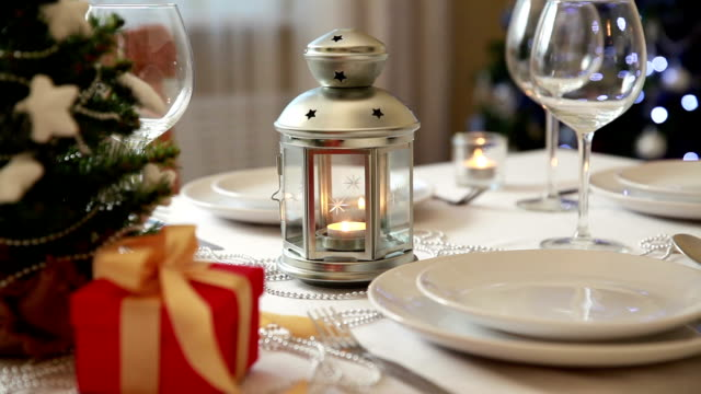 Christmas theme. Festive table setting with candles, gifts and Christmas lantern video
