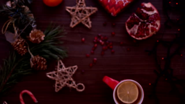 Christmas top view. Christmas decoration, christmas lights, tea and pomegranate on wooden table. Shot from above video