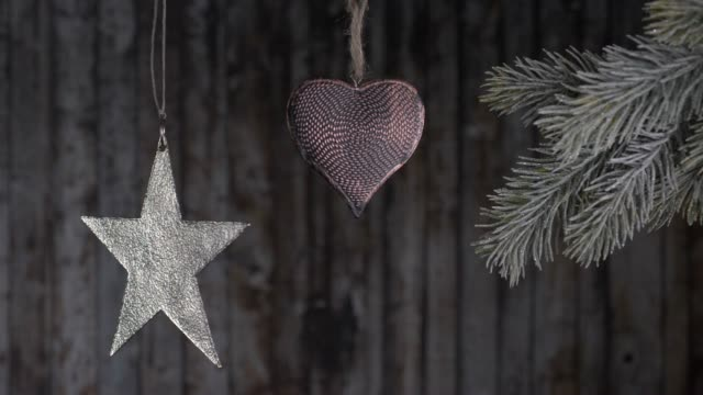 Christmas toys hanging on a branch of a Christmas tree on a wooden background. video