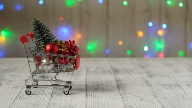 Christmas tree and gifts in a mini shopping cart on the background of led lamps garland.