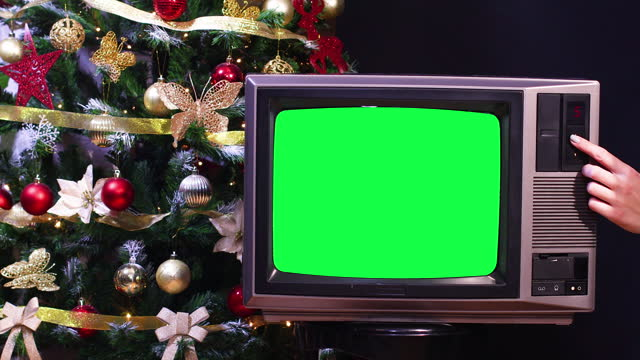 Christmas tree behind vintage old tv with green screen