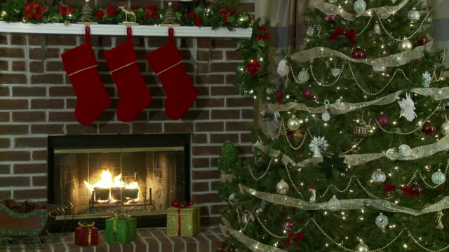 Christmas Tree by a Fireplace Tranquil medium-wide shot of a Christmas tree beside a burning fireplace. christmas stocking stock videos & royalty-free footage