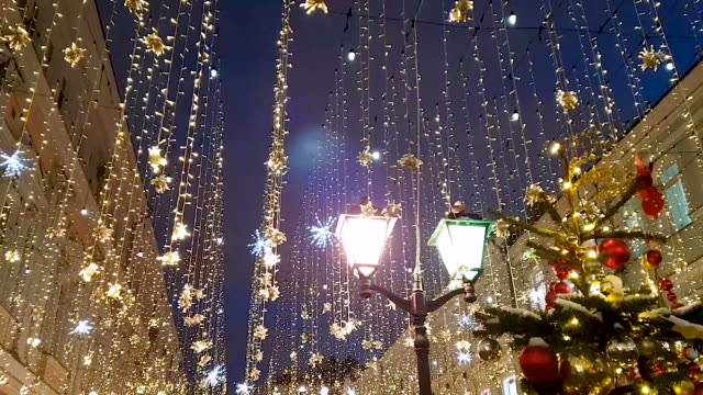 ein weihnachtsbaum auf der kuznetsky most street in moskau vor dem hintergrund flackernder girlanden und straßenlaternen. - girlande dekoration stock-videos und b-roll-filmmaterial