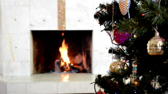 Christmas tree with decoration on background of burning fireplace video